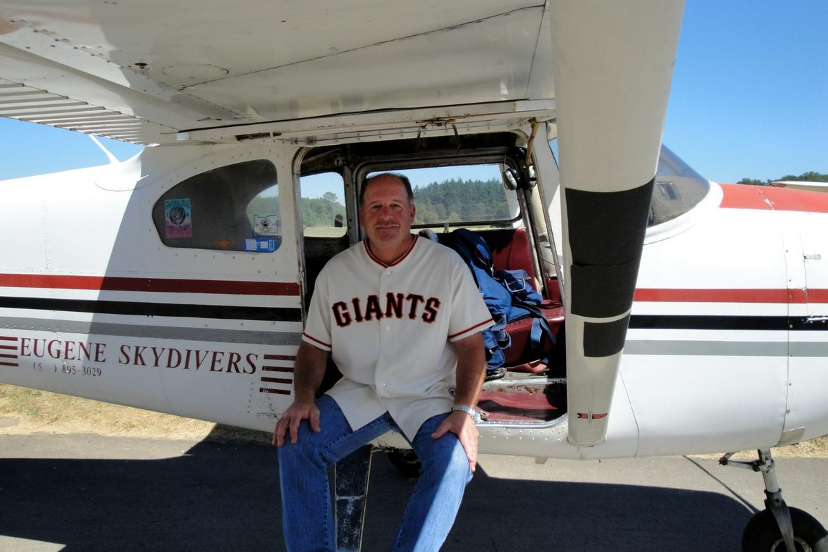man with Giants jersey sits in the door of Eugene Skydiver's Cessna plane