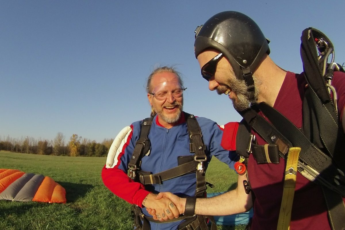 instructor and tandem skydiving student smile and shake hands in landing area after skydive