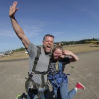 couple poses together in front of the camera before their skydive