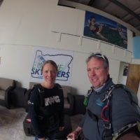 Mark and woman smile in front of Eugene Skydivers sign in the hangar