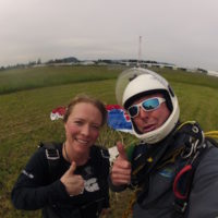 Mark and skydiving student gives thumbs up in landing area after making skydive