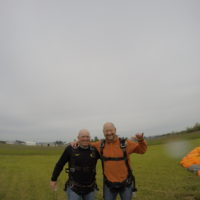 man and his instructor hug and smile after landing from tandem skydive