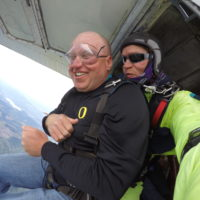 man smiles nervously before exiting the skydiving plane at Eugene Skydivers