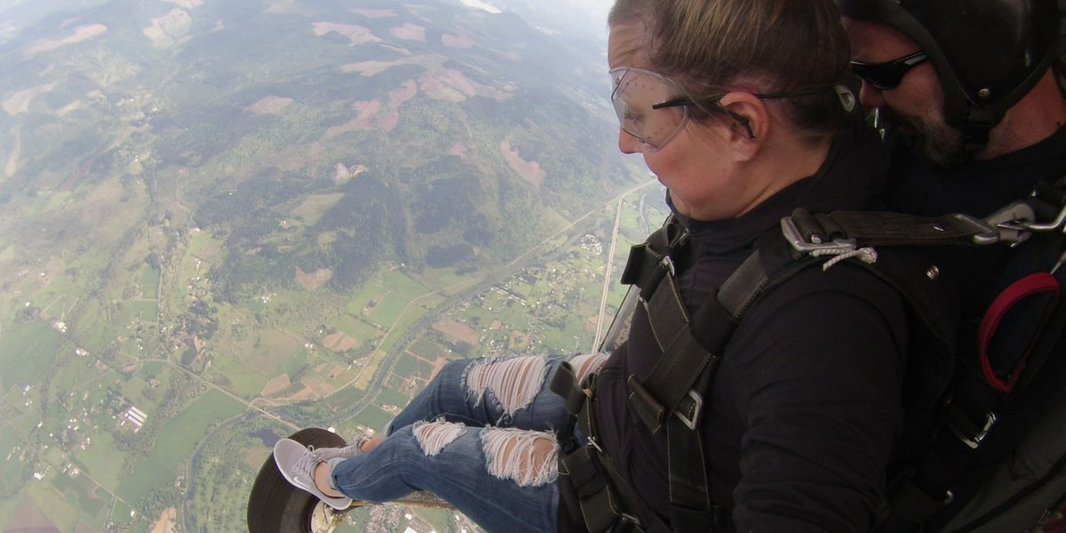 young woman places her feet on side of the aircraft before exiting into skydiving freefall