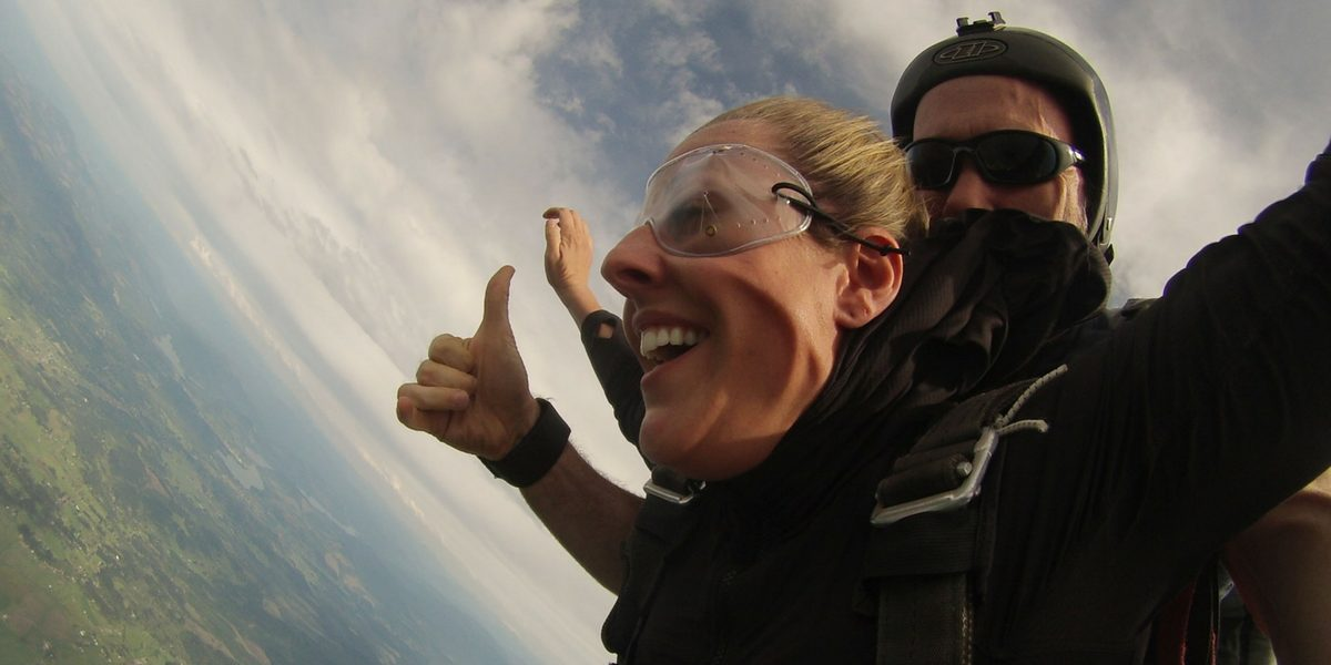 woman gives thumbs up in tandem skydiving freefall