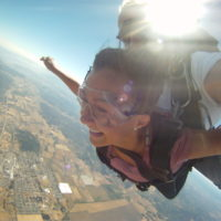 young woman smiles as she freefalls over the Willamette Valley in Oregon