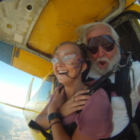 woman smiles and crosses her arms over her chest before exiting skydiving aircraft