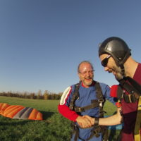 instructor shakes the hand of his skydiving student in landing area after skydive