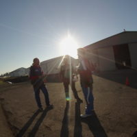 three men stand in front of the hangar while waiting to board the plane to make a tandem skydive