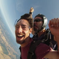 man smiles ear to ear while in tandem skydiving freefall
