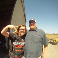 woman gives peace sign in front of skydiving hangar at Eugene Skydivers