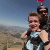 young man smiles under canopy during tandem skydive