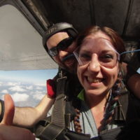 young woman smiles with instructor before exiting skydiving plane