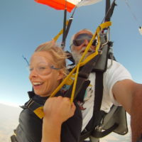 blond woman smiles under canopy making first ever tandem skydive