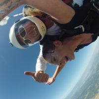Mark gives thumbs up while in freefall with tandem skydiving student