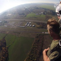tandem student soars over landing area during sunset at Eugene Skydivers