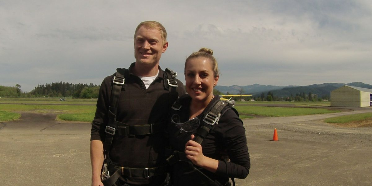 couple poses in front of hangar all geared up for their first tandem skydive