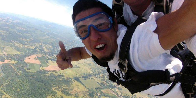 young man smiles during skydiving freefall at Eugene Skydivers